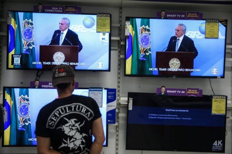 Sao Paulo, 2017. május 19. Michel Temer brazil elnök a nemzethez intézett televíziós beszédét követi egy férfi Sao Paulóban 2017. május 18-án. Az államfõ beszédében határozottan kijelentette, hogy nem mond le, dacára annak, hogy a brazil legfelsõbb bíróság engedélyezte a nyomozást ellene egy vesztegetési ügyben. Sajtóhírek szerint egy befolyásos brazil üzletember az ügyészséggel kötött vádalku keretében tett vallomása szerint Temer egy tanú megvesztegetéséhez járult hozzá, hogy az illetõ hallgasson a Petrobras brazil olajvállalat korrupciós botrányának ügyében. A brazil O Globo napilap szerint hangfelvétel van az elhangzottakról. (MTI/EPA/Fernando Bizerra Jr.)