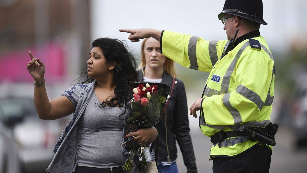 A police officer (R) directs a woman carrying a bunch of flowers near the Manchester Arena in Manchester, northwest England on May 23, 2017 following a deadly terror attack at the concert at the venue the night before. Twenty two people have been killed and dozens injured in Britain's deadliest terror attack in over a decade after a suspected suicide bomber targeted fans leaving a concert of US singer Ariana Grande in Manchester. / AFP PHOTO / Oli SCARFF