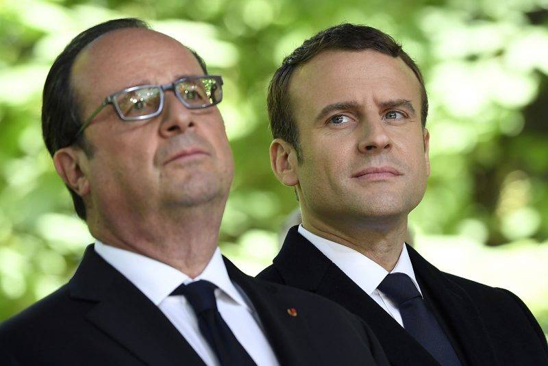 French President Francois Hollande (L) and newly elected president Emmanuel Macron look on during a ceremony to mark the anniversary of the abolition of slavery and to pay tribute to the victims of the slave trade on May 10, 2017 at the Jardins du Luxembourg in Paris. / AFP PHOTO / POOL / Eric FEFERBERG