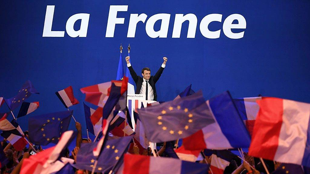 (FILES) This file photo taken on April 23, 2017 shows French presidential election candidate for the En Marche ! movement Emmanuel Macron raising his arms during a meeting at the Parc des Expositions in Paris after the first round of the presidential election.Emmanuel Macron was elected French president on May 7, 2017 in a resounding victory over far-right rival, after a deeply divisive campaign, initial estimates showed. / AFP PHOTO / Eric FEFERBERG