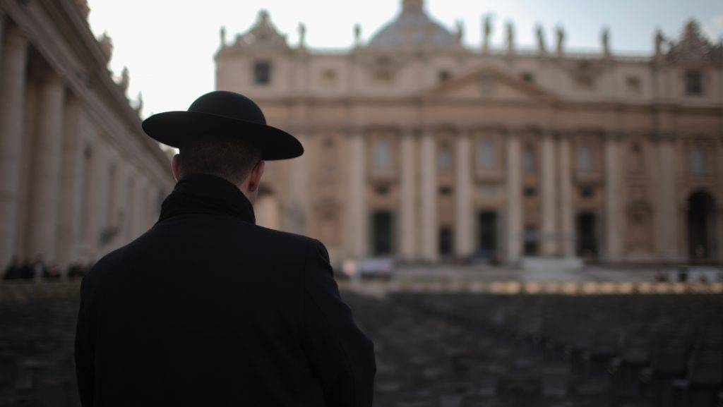 VATICAN CITY, VATICAN - FEBRUARY 26:  A priest stands next to St Peter's Basilica on February 26, 2013 in Rome, Italy. The Pontiff will hold his last weekly public audience on February 27, 2013 before he retires the following day. Pope Benedict XVI has been the leader of the Catholic Church for eight years and is the first Pope to retire since 1415. He cites ailing health as his reason for retirement and will spend the rest of his life in solitude away from public engagements.  (Photo by Christopher Furlong/Getty Images)