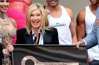 """LAS VEGAS, NV - APRIL 02:  Entertainer Olivia Newton-John reacts as she receives a ceremonial key to the Las Vegas Strip during a welcome event at Flamingo Las Vegas on April 2, 2014 in Las Vegas, Nevada. Newton-John will launch her residency show """"Summer Nights"""" on April 8.  (Photo by Ethan Miller/Getty Images)"""