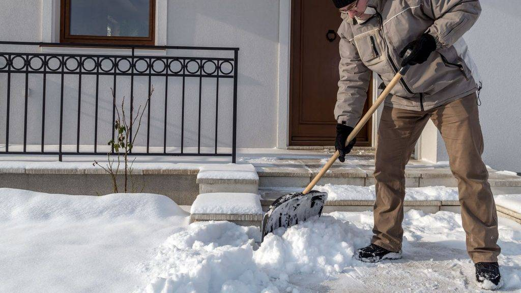 32839052 - man clearing path to his house of snow with shovel after heavy snowing