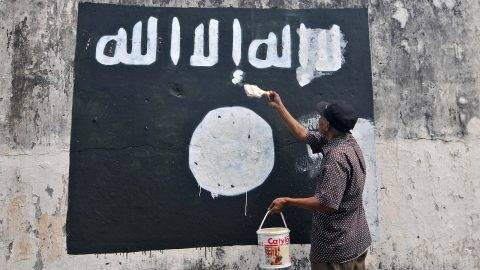 INDONESIA, Surakarta City: A government worker removes ISIS (Islamic State of Iraq and Syria) flags painted on to walls near Veteran Street in Surakarta City in an attempt to discourage the promotion of the jihadist group in the region. CITIZENSIDE/AGOES RUDIANTO