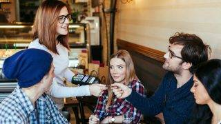 Beautiful Waitress Charging Customers Bill With A Credit Card Terminal