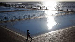 Fokváros, 2017. március 19. Egy kisfiú megy el a Sea Point tengerparti uszoda medencéinél a dél-afrikai Fokvárosban 2017. március 18-án napnyugtakor. (MTI/EPA/Kim Ludbrook)