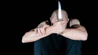 Suicide. Suicidal man in the dark holding knife in his hand. Dark image. Dark background. Selective focus.