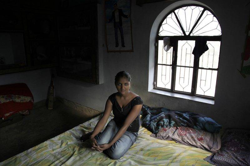 INGONIA, INDIA - NOVEMBER 16:  Sapana Nahala, 22, a sex worker, poses at her house November 16, 2009 in Ingonia, Rajasthan, India. The small village is inhabited by the Nats caste, whose women were traditionally dancers to feudal lords. When the feudal system was abolished, they lost their patrons and over time many were compelled to take up prostitution while the men lived off of their earnings. Adolescent girls are initiated into the family 'tradition' while their brothers become 'agents'. They may practice locally or in big cities such as Delhi and Mumbai as bar girls or in brothels.  (Photo by Kuni Takahashi/Getty Images)