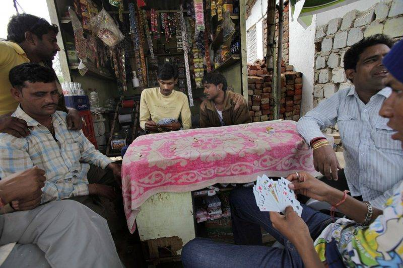 INGONIA, INDIA - NOVEMBER 16:  Men play cards November 16, 2009 in Ingonia, Rajasthan, India. The small village is inhabited by the Nats caste, whose women were traditionally dancers to feudal lords. When the feudal system was abolished, they lost their patrons and over time many were compelled to take up prostitution while the men lived off of their earnings. Adolescent girls are initiated into the family 'tradition' while their brothers become 'agents'. They may practice locally or in big cities such as Delhi and Mumbai as bar girls or in brothels.  (Photo by Kuni Takahashi/Getty Images)
