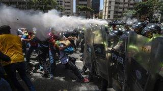 Venezuela's opposition activists clash with riot police agents during a protest against Nicolas Maduro's government in Caracas on April 4, 2017.Protesters clashed with police in Venezuela Tuesday as the opposition mobilized against moves to tighten President Nicolas Maduro's grip on power. Protesters hurled stones at riot police who fired tear gas as they blocked the demonstrators from advancing through central Caracas, where pro-government activists were also planning to march. / AFP PHOTO / JUAN BARRETO