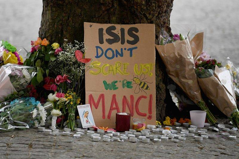 MANCHESTER, ENGLAND - MAY 24:  Members of the public pause to look at floral tributes and messages as the working day begins on May 24, 2017 in Manchester, England. An explosion occurred at Manchester Arena on the evening of May 22 as concert goers were leaving the venue after Ariana Grande had performed. Greater Manchester Police are treating the explosion as a terrorist attack and have confirmed 22 fatalities and 59 injured.  (Photo by Jeff J Mitchell/Getty Images)