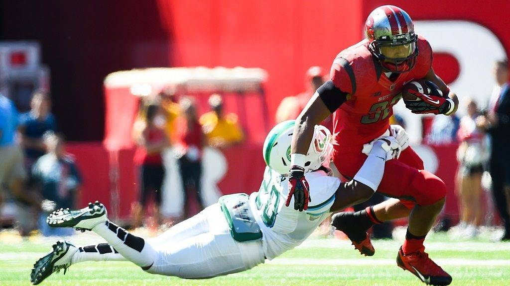 PISCATAWAY, NJ - SEPTEMBER 27: Justin Goodwin #32 of the Rutgers Scarlet Knights attempts to run past Nico Marley #20 of the Tulane Green Wave in the second quarter at High Point Solutions Stadium on September 27, 2014 in Piscataway, New Jersey.   Alex Goodlett/Getty Images/AFP
