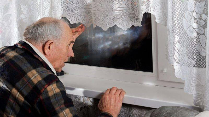 Senior man peering through a window at night as he watches for someone to arrive