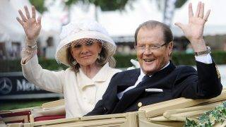 Picture taken on June 25, 2013 in Aachen, western Germany, shows British actor and UNICEF Goodwill Ambassador Roger Moore and his Danish wife Kristina Tholstrup waving from a carriage as they visit the CHIO World Equestrian Festival.Moore, who will forever be remembered for playing the womanising superspy James Bond, died May 23, 2017, aged 89, his family announced in a statement. / AFP PHOTO / dpa / Henning Kaiser / Germany OUT