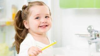 21965611 - smiling child girl brushing teeth in bathroom