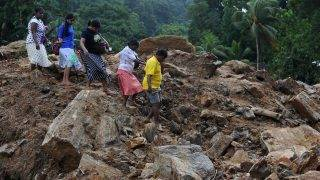 Sri Lankan villagers cross a landslide site as military rescue workers and villagers search for survivors in Athweltota village in Kalutara on May 28, 2017. Emergency teams rushed to distribute aid on May 28 to half a million Sri Lankans displaced after the island's worst flooding in more than a decade claimed 126 lives and left scores more missing. / AFP PHOTO / LAKRUWAN WANNIARACHCHI