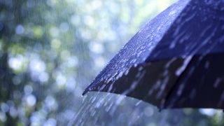 Rain drops falling from a black umbrella