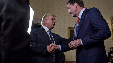 """United States President Donald Trump, center, shakes hands with James Comey, director of the Federal Bureau of Investigation (FBI), during an Inaugural Law Enforcement Officers and First Responders Reception in the Blue Room of the White House in Washington, D.C., U.S., on Sunday, Jan. 22, 2017. Trump earlier today mocked protesters who gathered for large demonstrations across the U.S. and the world on Saturday to signal discontent with his leadership, but later offered a more conciliatory tone, saying he recognized such marches as a """"hallmark of our democracy."""" Credit: Andrew Harrer / Pool via CNP - NOWIRESERVICE- Photo: Andrew Harrer/Pool via CNP/Consolidated/dpa"""