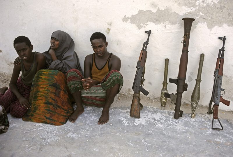 Suspected Al Qaeda-aligned Shabaab militants, a woman and her three children, sit next to weapons after their arrest on May 5, 2016 in Mogadishu.Somali security forces presented to journalists a family suspected of belonging to the Somalia-based al-Qaeda affiliated Islamist militant group Al-Shabaab. Members of this family were arrested with two AK-47 assault rifles and a rocket during an operation by Somali security forces against suspected members of of Somalia's Shebab Islamists in the capital Mogadishu. / AFP PHOTO / MOHAMED ABDIWAHAB