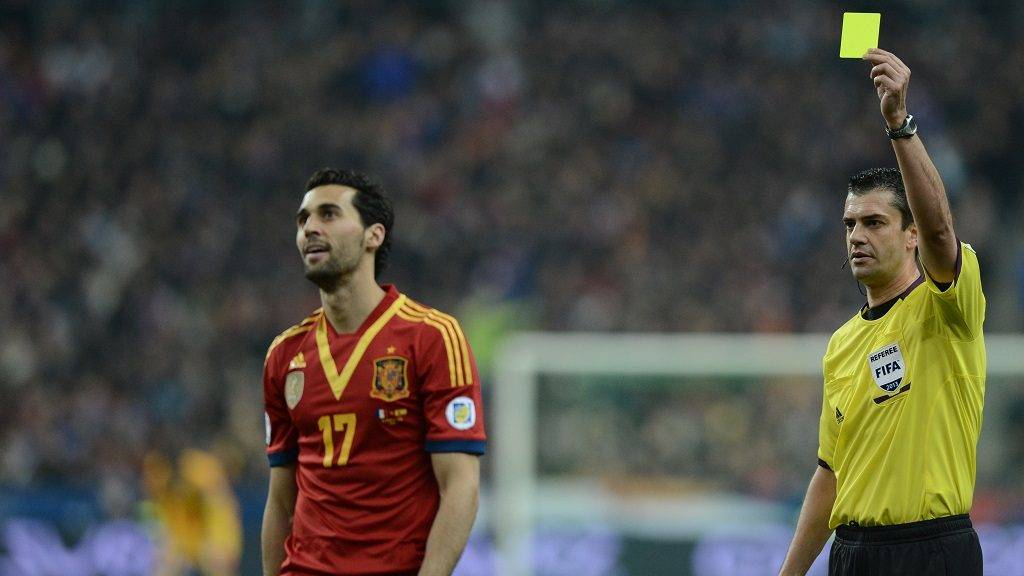 Hungarian referee Viktor Kassai (R) gives a yellow card to Spain's defender Alvaro Arbeloa  during the World Cup 2014 qualifying football match France vs Spain on March 26, 2013 at the Stade de France in Saint-Denis, outside Paris.   AFP PHOTO / FRANCK FIFE / AFP PHOTO / FRANCK FIFE