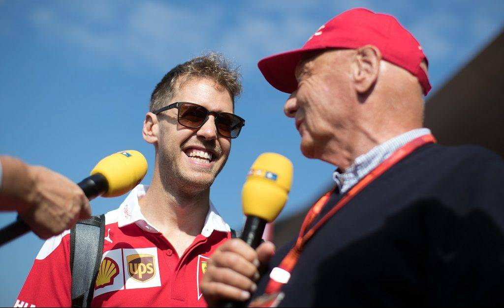 Scuderia Ferrari German driver Sebastian Vettel (L) and Niki Lauda speak at the Red Carpet prior the third training session for the Formula One Grand Prix of Austria on July 2, 2016, in Spielberg ahead of the Formula One Grand Prix of Austria taking place on July 3, 2016.  / AFP PHOTO / APA / GEORG HOCHMUTH / Austria OUT