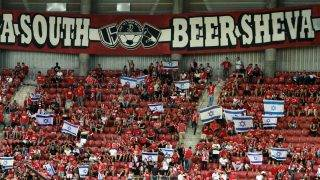 Hapoel Beer Sheva fans wave Israeli flags before the UEFA Champions League group stages  play-off football match between Celtic and Hapoel Beer Sheva at the Turner Stadium in the southern Israeli city of Beer Sheva on August 23, 2016.   The game is being played in the most southerly stadium in European competition history, UEFA confirmed.   / AFP PHOTO / GIL COHEN-MAGEN