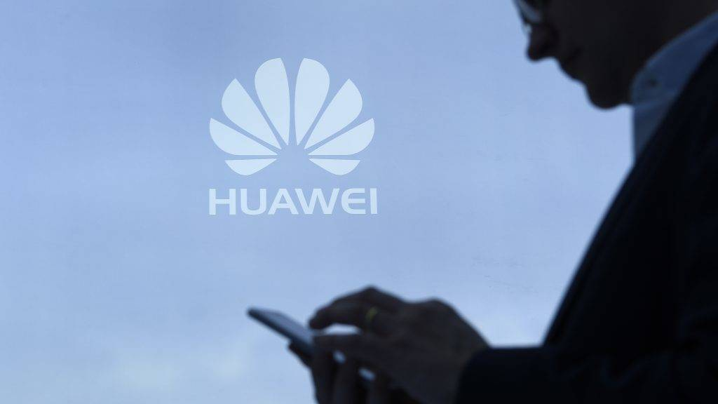 A visitor uses his mobile phone at the Huawei stand on the second day of the Mobile World Congress on February 28, 2017 in Barcelona. Phone makers will seek to seduce new buyers with artificial intelligence functions and other innovations at the world's biggest mobile fair starting today in Spain. / AFP PHOTO / LLUIS GENE
