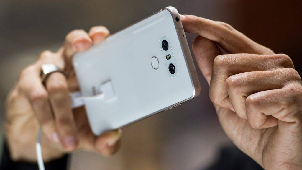 A visitor takes a picture with the Dual rear-facing cameras located on the back of a LG G6 smartphone, manufactured by LG Electronics Inc. during the Mobile World Congress on the third day of the MWC in Barcelona, on March 1, 2017.  Phone makers will seek to seduce new buyers with artificial intelligence functions and other innovations at the world's biggest mobile fair starting today in Spain. / AFP PHOTO / Josep LAGO