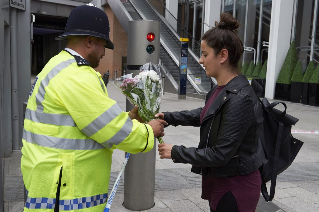 A man asks a police officer to lay flowers outside The Shard in the London Bridge quarter in London on June 4, 2017, as a tribute to the victims of the June 3 terror attack. Seven people were killed in a terror attack on Saturday by three assailants on London Bridge and in the bustling Borough Market nightlife district, the chief of London's police force said on Sunday. / AFP PHOTO / NIKLAS HALLE'N