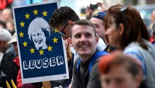 "A demonstrator holds a placard depicting an image of Britain's Prime Minister Theresa May, surrounded by the stars of the EU flag and with the words ""Leuser"", as he stands outside the entrance to Downing Street, in central London on June 9, 2017, following the result of the general election. A defiant Prime Minister Theresa May vowed Friday to form a new government to lead Britain out of the EU despite losing her majority in a snap general election and facing calls to resign. Although winning the most seats, May's centre-right Conservative party lost its majority in parliament, meaning it will now rely on support from Northern Ireland's Democratic Unionist Party (DUP). / AFP PHOTO / Glyn KIRK"