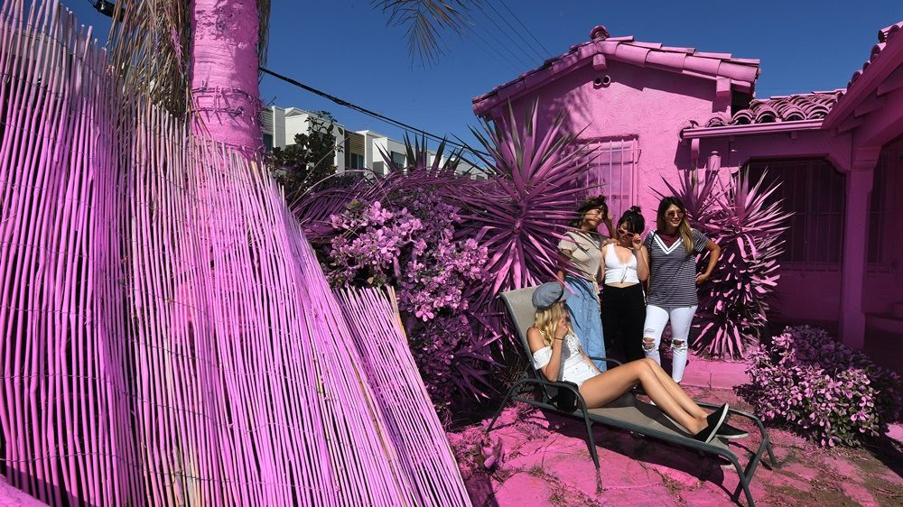 """People pose for photos outside the """"Pink Houses"""" which have become an pop-up photo opportunity after a local developer hired artist Matty Mo to paint the three houses pink, before their eventual demolition in Los Angeles, California on June 16, 2017. The local neighborhood committee is pushing to have the houses painted in a more subdued color before demolition work begins. / AFP PHOTO / Mark RALSTON"""