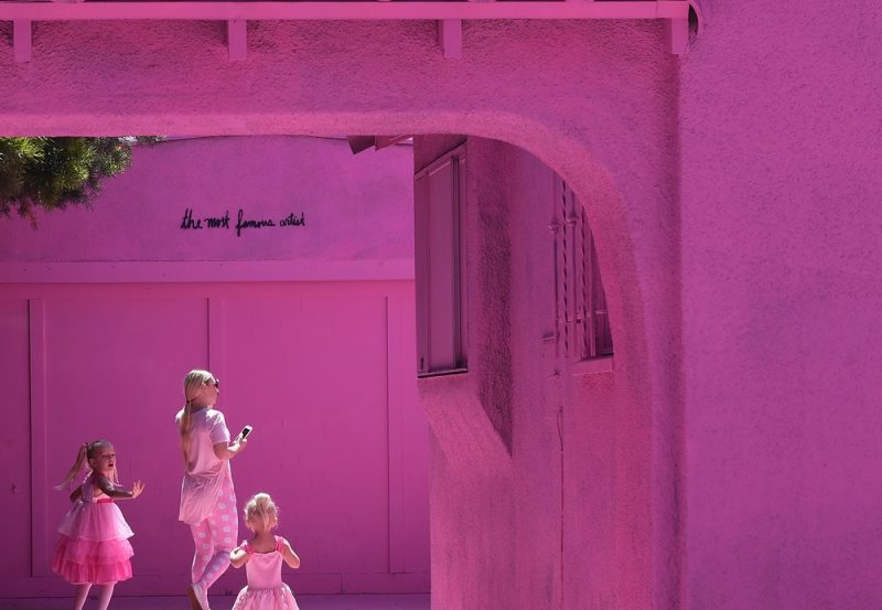 """People pose for photos outside the """"Pink Houses"""" which have become an pop-up photo opportunity after a local developer hired artist Matty Mo to paint the three houses pink, before there eventual demolition in Los Angeles, California on June 16, 2017. The local neighborhood committee is pushing to have the houses painted in a more subdued color before demolition work begins. / AFP PHOTO / Mark RALSTON"""