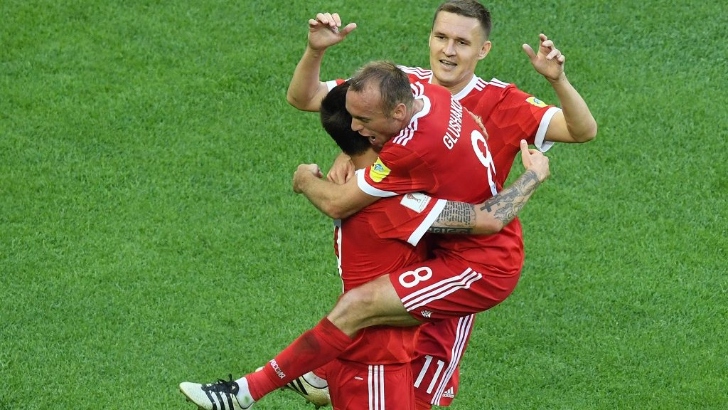 Russia's midfielder Denis Glushakov (R-8) hugs Russia's forward Fedor Smolov as they celebrate the team's second goal during the 2017 Confederations Cup group A football match between Russia and New Zealand at the Krestovsky Stadium in Saint-Petersburg on June 17, 2017. / AFP PHOTO / FRANCOIS XAVIER MARIT