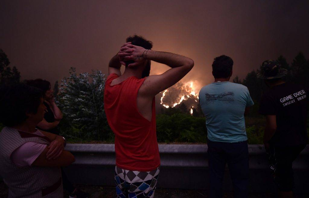 Villagers look at flames during a wildfire near the village of Mega Fundeira on June 18, 2017. 