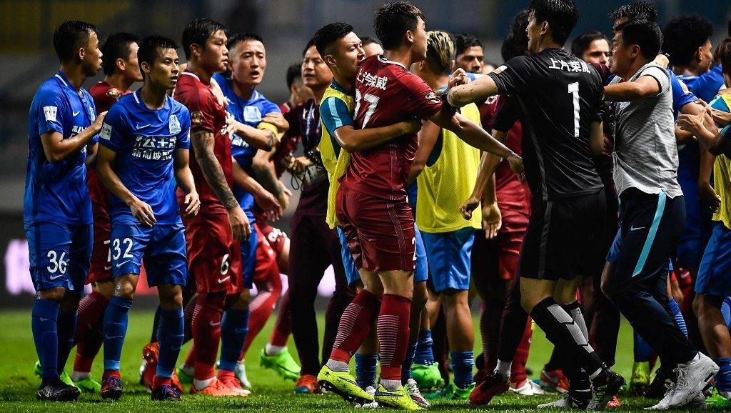 This photo taken on June 18, 2017 shows a brawl between Shanghai SIPG players (in red) and Guangzhou R&F players (in blue), during their Chinese Super League football match in Guangzhou, in China's southern Guangdong province.  Brazilian international Oscar triggered a mass brawl in the Chinese Super League as players and staff from his Shanghai SIPG side and opponents Guangzhou R&F scrapped on the pitch. / AFP PHOTO / STR / China OUT