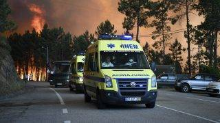 Ambulances lead the way during the evacuation of Picha, as a wildfire approaches the village near Pedrogao Grande on June 20, 2017. The huge forest fire that erupted on June 17, 2017 in central Portugal killed at least 64 people and injured 135 more, with many trapped in their cars by the flames.   / AFP PHOTO / FRANCISCO LEONG