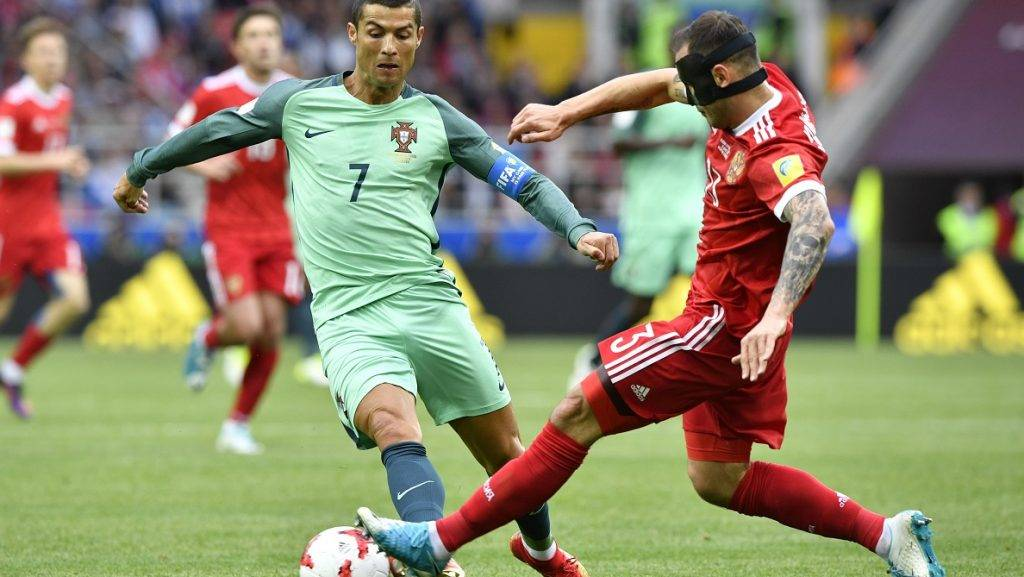 Portugal's forward Cristiano Ronaldo (L) vies with Russia's defender Fedor Kudryashov during the 2017 Confederations Cup group A football match between Russia and Portugal at the Spartak Stadium in Moscow on June 21, 2017. / AFP PHOTO / Alexander NEMENOV