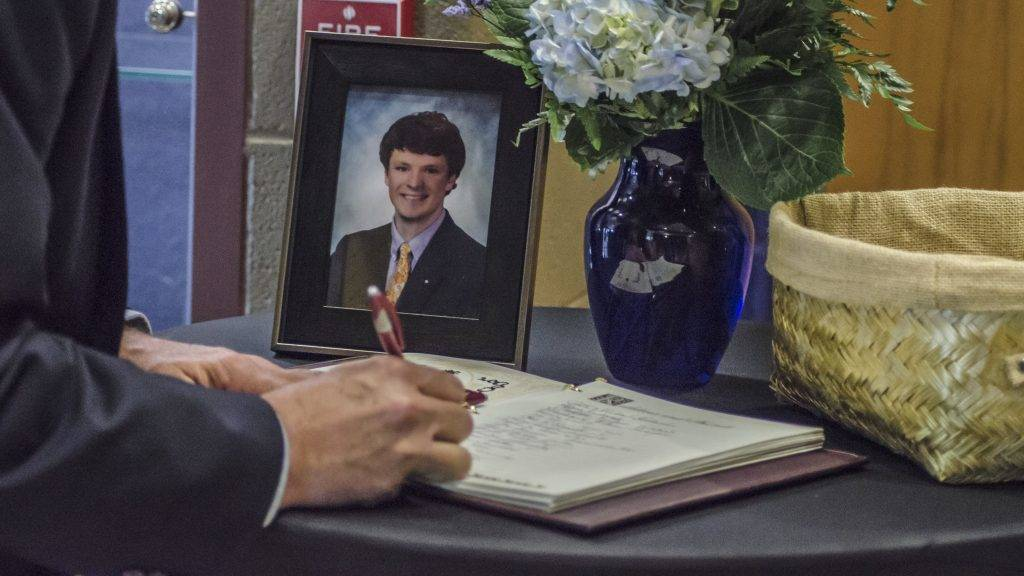 """This handout photo obtained courtesy of the Warmbier family shows a mourner signing a guest book at Wyoming High School in Wyoming, Ohio, on June 22, 2017, during the funeral for Otto Warmbier.  Warmbier an American university student who, while visiting North Korea as a tourist in January 2016, was arrested and sentenced to 15 years of hard labor after being accused of stealing a propaganda poster. Warmbier died on June 19, 2017 six days after retuning to the United States in a coma.  / AFP PHOTO / FAMILY HANDOUT / Handout / RESTRICTED TO EDITORIAL USE - MANDATORY CREDIT """"AFP PHOTO / THE WARMBIER FAMILY"""" - NO MARKETING NO ADVERTISING CAMPAIGNS - DISTRIBUTED AS A SERVICE TO CLIENTS"""