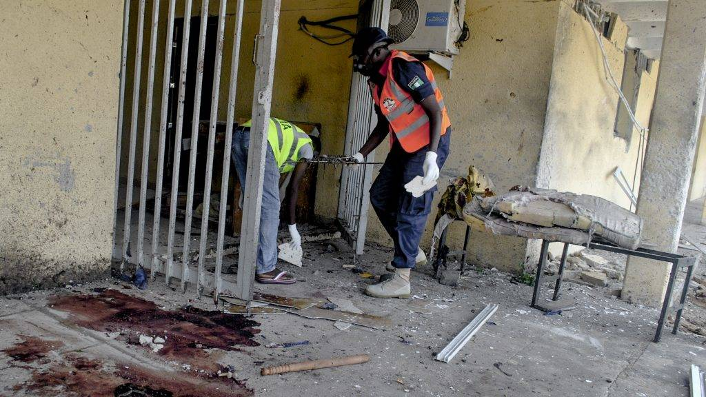 Emergency personnel are at work at the site of a blast at the campus of Maiduguri University and residential buildings on June 26, 2017.  Nine people have been killed in a string of suicide attacks in Maiduguri, a city in Nigeria's restive northeast where Boko Haram Islamists began a deadly insurgency in 2009, police said. The attacks occurred as Nigeria began a two-day public holiday for Eid al-Fitr which marks the end of the Muslim holy fasting month of Ramadan. / AFP PHOTO / STRINGER