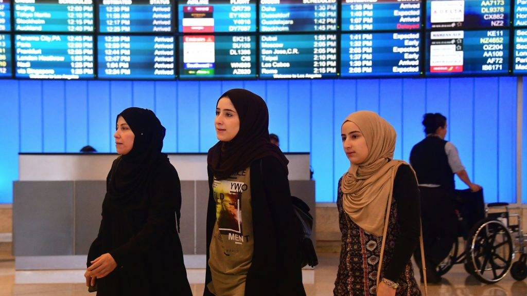 Travellers from the Middle East arrive at the International Arrivals section at Los Angeles International Airport on June 29, 2017, where free legal advice was offered and activists protested President Donald Trump's ban temporarily barring entry into the US from Libya, Iran, Somalia, Sudan, Syria and Yemen.  The ban prevents the issuance of visas to travelers from the six countries for 90 days and places the refugee-entry program on hold for 120 days. / AFP PHOTO / FREDERIC J. BROWN