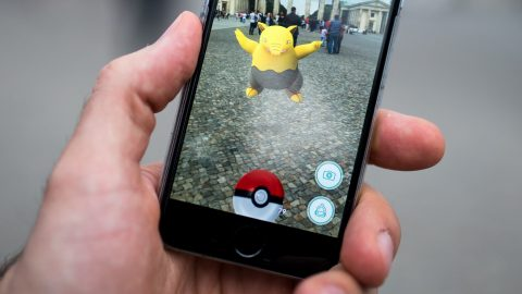 A man tries to catch the pokèmon 'Traumato' using the app 'Pokèmon Go' in front of Brandenburg Gate in Berlin, Germany, 13 July 2016. The app has been available in German app stores since 13 July. The app allows users to collect pokèmon and fight against each other. Photo: Alexander Heinl/dpa