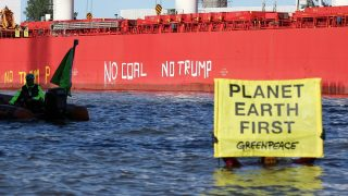 """Greenpeace activists demonstrate in front of the freighter """"SBISubaru"""" holding a banner with the inscription """"Planet Earth First""""on a boat on the river Elbe in Hamburg, Germany, 01 June 2017. The activists had previously followed the freighter on inflatable rafts and wrote the inscriptions """"No Coal"""" and """"No Trump"""" on the freighter's hull. The activists protested on Thursday against US President Donald Trump's expected decision to withdraw from the Paris Climate Accord. According to Greenpeace the freighter ship carried around 60,000 tonnes of coal from Texas to Germany. Photo: Bodo Marks/dpa"""