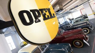The Opel-logo is prominently displayed above vintage cars inside the Opel Classic Garage on the factory grounds of car builder Opel in Ruesselsheim, Germany, 10 June 2017. Photo: Arne Dedert/dpa