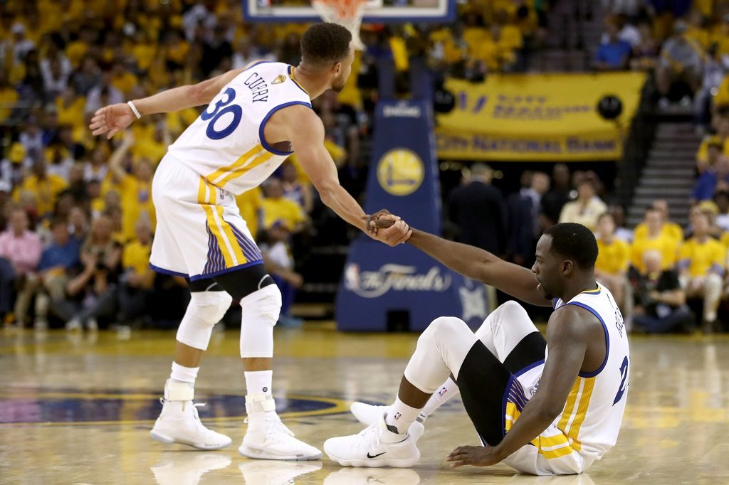 OAKLAND, CA - JUNE 04: Kevin Durant #35 is helped to his feet by Stephen Curry #30 of the Golden State Warriors against the Cleveland Cavaliers during the second half of Game 2 of the 2017 NBA Finals at ORACLE Arena on June 4, 2017 in Oakland, California. NOTE TO USER: User expressly acknowledges and agrees that, by downloading and or using this photograph, User is consenting to the terms and conditions of the Getty Images License Agreement.   Ezra Shaw/Getty Images/AFP