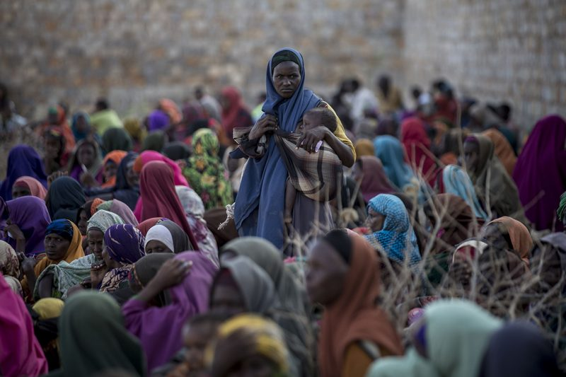 UNSPECIFIED, SOMALIA - MARCH 27: A Somalian woman holds her baby as others sit on the ground at Balanbaalis camp in Somalia's Bay state on March 27, 2017. In the central and south parts of Somalia, extreme drought threatens to leave many people hungry and vulnerable to disease epidemics. Somalians forced to live in the Balanbaalis camp in Somalia's Bay state due to clashes and terror in the country are fighting drought and disease from makeshift tents. As there are very limited water sources in the region, people are queuing for water at wells drilled by aid organizations. Arif Hudaverdi Yaman / Anadolu Agency