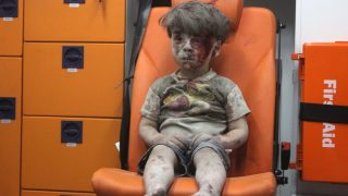 ALEPPO, SYRIA - AUGUST 17 :  5-year-old wounded Syrian kid Omran Daqneesh sits alone in the back of the ambulance after he got injured during Russian or Assad regime forces air strike targeting the Qaterji neighbourhood of Aleppo on August 17, 2016. Mahmud Rslan / Anadolu Agency