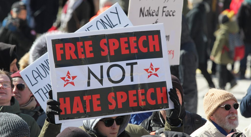 Pro-Muslim protestor carrying a sign saying 'Free Speech NOT Hate Speech' as opposing groups of protesters clashed over the M-103 motion to fight Islamophobia during pro-Muslim and anti-Muslim demonstrations in downtown Toronto; Ontario; Canada; on March 04; 2017. Canadians across the country staged similar protests against Islam; Muslims; Sharia Law and M-103. These protests were met by counter protests by those supporting Muslims and in favour of M-103. M-103 is a private members motion put forth by Liberal MP Iqra Khalid that asks the government to 'recognize the need to quell the increasing public climate of hate and fear' and condemn Islamophobia; as well as all other kinds of 'systemic racism and religious discrimination.' (Photo by Creative Touch Imaging Ltd./NurPhoto)
