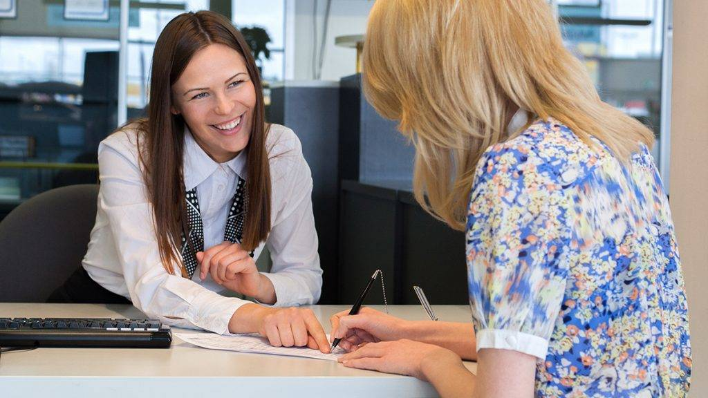 Two happy business women talking and signing credit or insurance in office