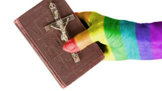 Hand (woman) holding a very old bible, isolated on white, rainbow flag