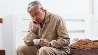 Worried senior man can not sleep. He is sitting on bed and drinking tea.